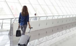 Woman-with-luggage-walking-through-airport